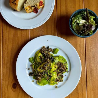 smoked mozzarella + basil ravioli in zucchini + basil fondue, with caramelized onions, fava beans, parsley, mint, + pistachio gremolata. applefield farms mixed greens with shaved radishes + lemon-dijon vinaigrette. housemade focaccia with blistered cherry tomatoes + basil.